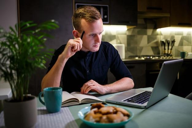 フリーランサーは自宅のキッチンでラップトップを使って仕事をしています。ラップトップで作業し、良いニュースを読んで成功した男。ハンサムな成功した起業家は彼の現代の家に座って働いています。