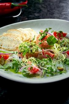 Французская закуска перед основным блюдом - тартар из стейка из лосося с авокадо, помидорами черри и гренками, подается в белой тарелке. ресторанная еда. вид сверху