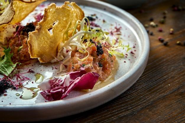 Французская закуска перед основным блюдом - тартар из стейка из лосося с черной икрой, сливочным сыром и гренками, подается в белой тарелке. ресторанная еда. вид сверху