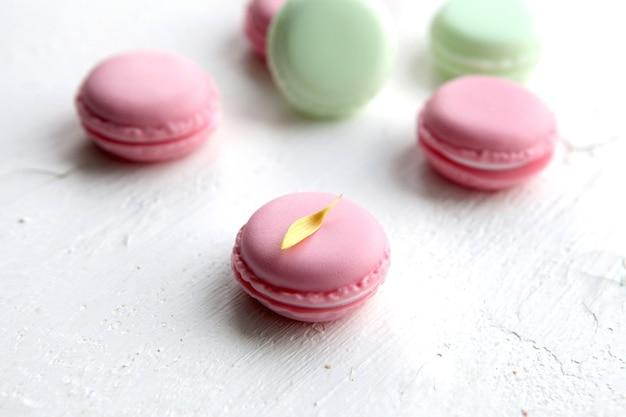 フランスの甘い珍味、白い背景に花が付いたカラフルなマカロンのバラエティのクローズアップ。美味しいマカロンのカラフルな食感。