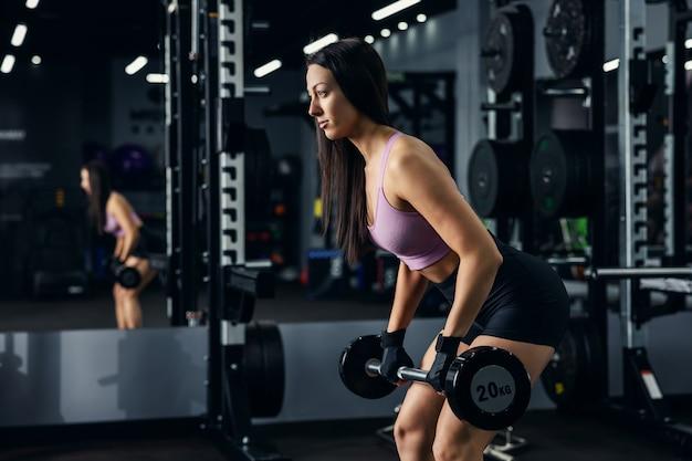 섹시 스포츠웨어를 입은 신선하고 매력적인 어린 소녀가 데드 리프트 위치에 있으며 웨이트 바벨을 들고 있습니다. 그녀는 들어 올릴 준비가되어 있고 강하고 집중 해 보입니다. 체육관 라이프 스타일
