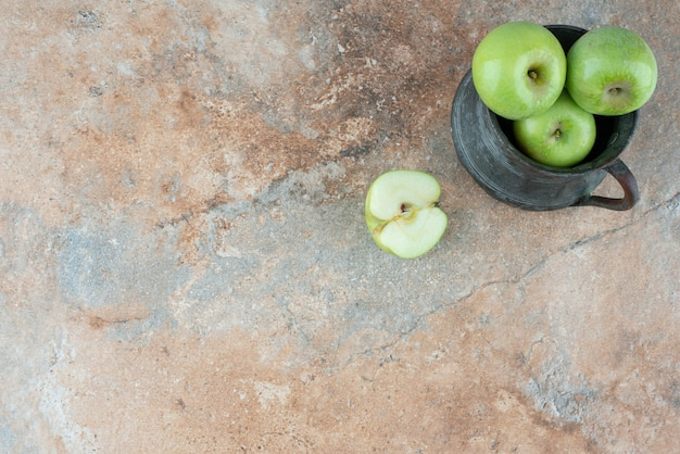 Свежие яблоки с древней чашкой на мраморном столе.