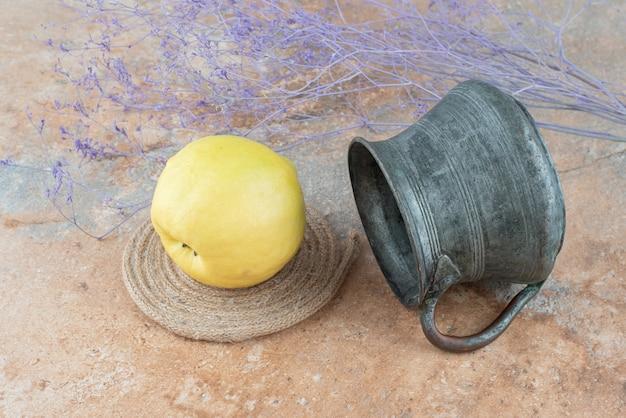 Свежая айва с древней чашкой на мраморном столе.