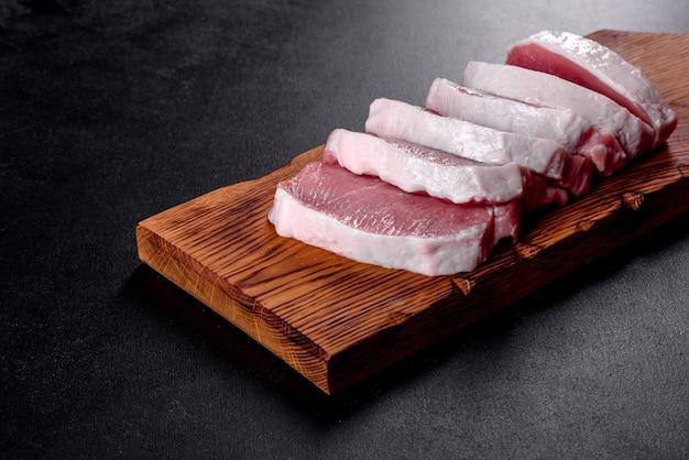 Свежий сырой кусок эскалопа из свинины разрезать на несколько частей