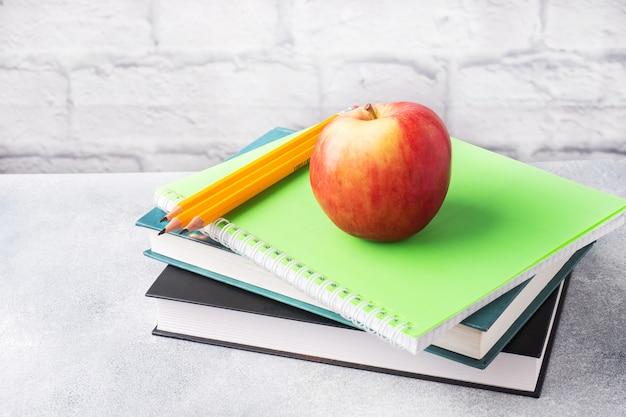 本やノートのスタックに新鮮な赤いリンゴ。学校の朝食のおやつのコンセプト。コピースペース、