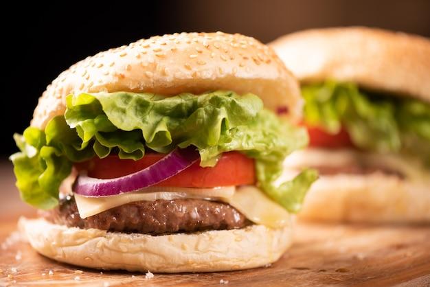 Свежий вкусный гамбургер и картофель на деревянном столе