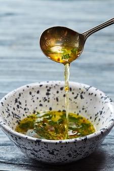 Свежеприготовленный салатный соус падает с ложки в керамическую миску с оливковым маслом, измельченными травами, солью, перцем, уксусом на сером деревянном фоне.