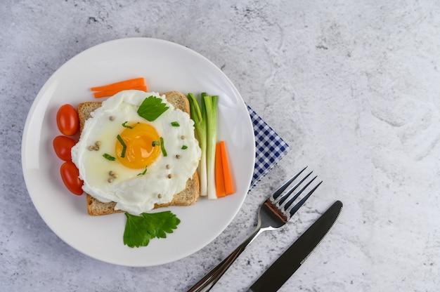 당근, 파와 고추 씨앗을 얹어 토스트에 누워 튀긴 계란.