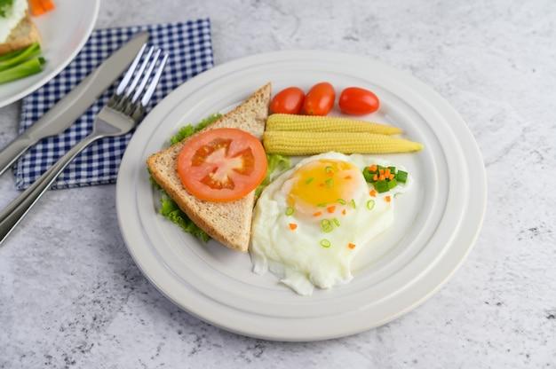 Жареное яйцо на тосте, посыпанное семенами перца с морковью, кукурузой и зеленым луком.