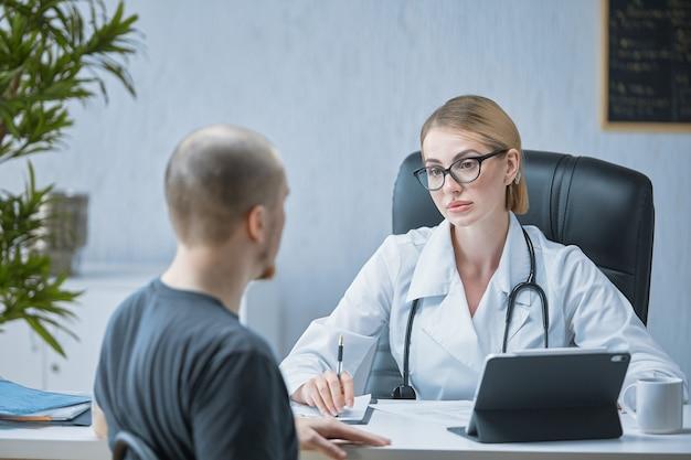 Приветливый врач выслушивает пациента в ярком и современном медицинском кабинете.