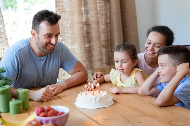 다정한 가족이 집에서 어린 소녀의 여섯 번째 생일을 축하합니다. 생일 소녀는 케이크에 있는 생일 초를 끌 준비를 하고 있습니다.