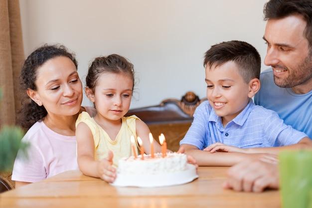 다정한 가족은 소녀의 6번째 생일을 축하하며 나무 테이블에 앉아 생일 소녀가 소원을 빌기를 기다리고 케이크의 생일 초에 불을 끕니다.