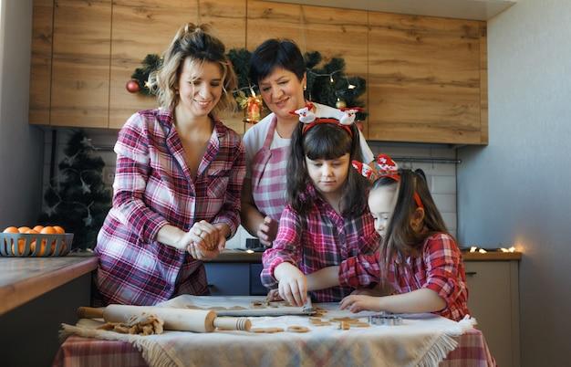 キッチンのフレンドリーな家族がクリスマスイブに生地からクッキーを準備します。