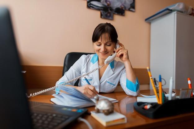 Приветливая женщина-врач сидит в своем кабинете, разговаривает по телефону с одной из пациенток и что-то записывает в блокнот. врач работает. понятие о медицине.