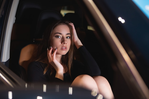 Испуганная девушка в салоне престижной машины