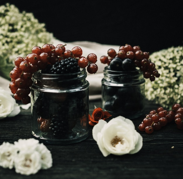 Фронт крупным планом вид свежих ягод ежевики и других ягод внутри стеклянных банок на темном дск