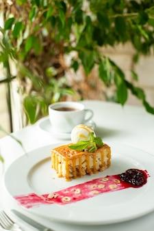 フロントクローズアップビュー小さなケーキは白い机の上の白い皿の中においしいデザイン