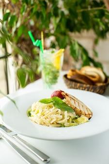 전면은 흰색 책상에 하얀 접시 안에 녹색 잎과 고기와 함께 맛있는 식사 요리 파스타를 볼 수 있습니다
