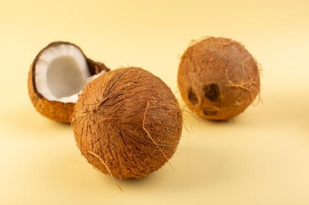 Фронт закрыл вид кокосовых орехов целого молочного свежего спелого, изолированных на кремовом фоне тропических экзотических фруктов орех