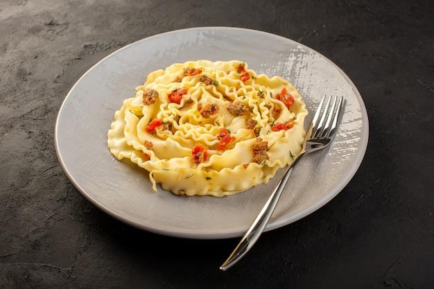 어두운 회색 접시 안에 요리 썰어 야채와 고기와 함께 전면 폐쇄 뷰 반죽 파스타
