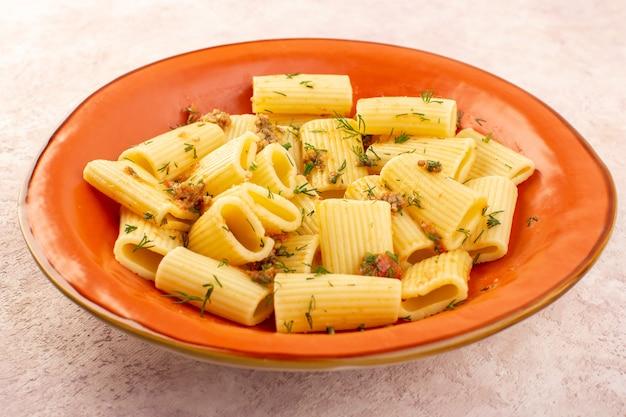 フロントのクローズアップビューイタリアパスタは乾燥した緑とおいしい調理し、ピンクの机の上の丸いオレンジプレートの内側に塩漬け