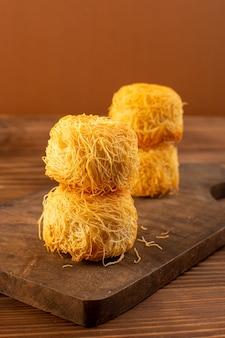 Передний закрытый вид вокруг сладких пирогов вкусные вкусные пирожные, изолированные выложены на коричневом деревянном деревенском столе
