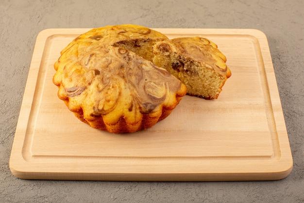 Фронт закрытый вид сладкий торт вкусный вкусный шоколадный торт нарезанный на кремового цвета квадратный стол