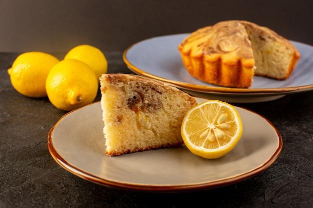 Фронт закрытый вид сладкий кусок торта вкусный вкусный кусочек торта шоколадный внутри бежевой тарелке вместе с желтыми лимонами