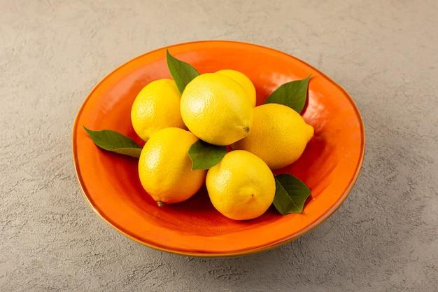 フロントクローズアップビュー黄色フレッシュレモン熟したまろやかなジューシーなグレーのオレンジプレート内