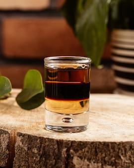 茶色の木製の机の上のガラスの中の正面アルコール飲料