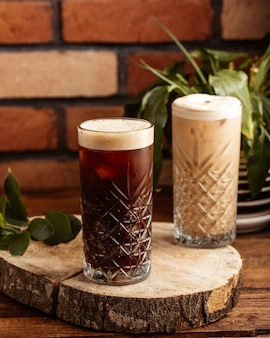 茶色の木製の机の上のグラスの中の正面アルコール飲料