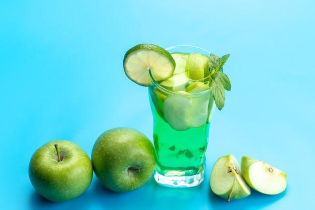 Яблочный коктейль, вид спереди, свежий и охлаждающий, вместе со свежими яблоками и дольками лимона на синем, свежем фруктовом соке