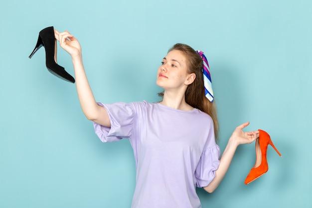 青に黒とオレンジの靴を保持している青いシャツドレスで正面の魅力的な女性