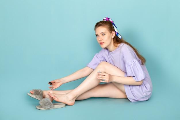 青いシャツのドレスで彼女の爪を青で扱う正面の魅力的な女性