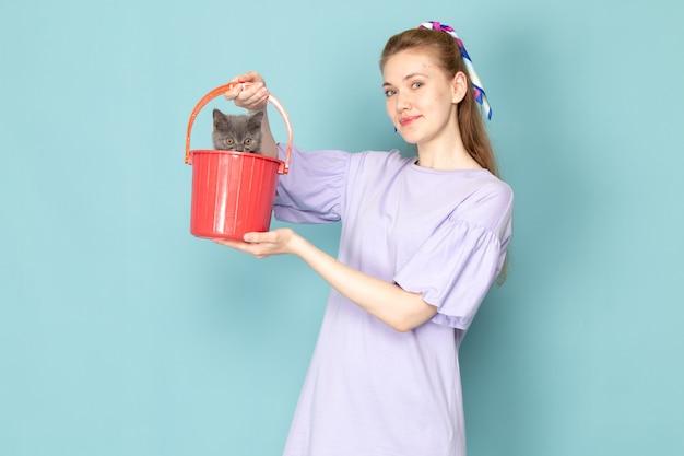 青にかわいい子猫と赤いバケツを保持している紫色のシャツで正面の魅力的な女性