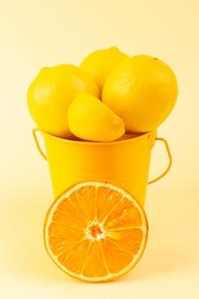 レモンが入った正面バスケットは、クリーム色の背景にオレンジのスライスとともに、新鮮でまろやかでジューシーなスライス全体をスライス