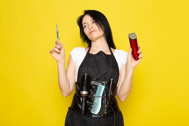 正面は、はさみと黄色の背景のスタイリスト理髪店の髪にポーズをとってマシンを保持している洗った髪とブラシで白いtシャツブラックケープの美しい女性美容師