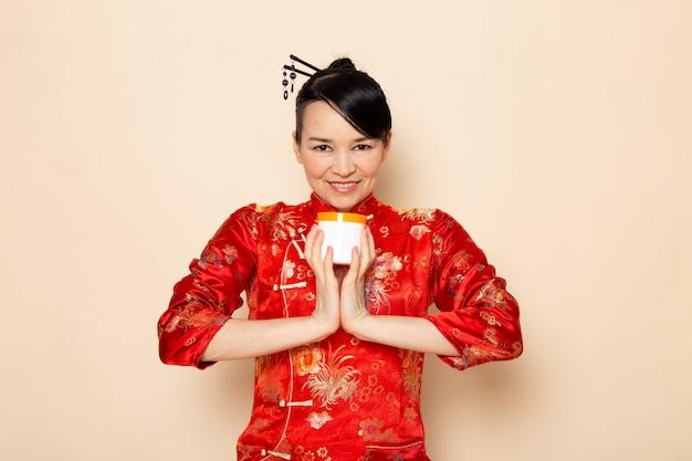 正面の美しい日本の芸者の伝統的な赤い和服で髪棒でポーズ笑顔笑顔幸せな保持クリーム缶クリーム背景式日本