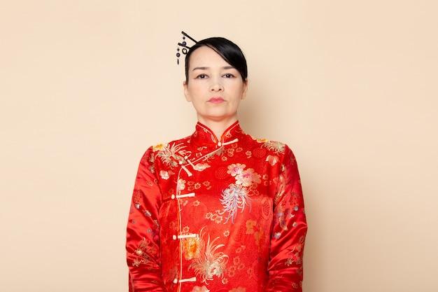 正面を飾るクリーム色の背景の上に立ってポーズをとって髪棒で伝統的な赤い和服の美しい日本の芸者