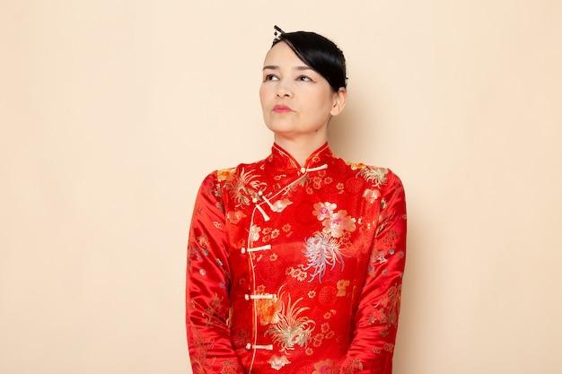 クリーム色の背景の上に立ってポーズをとって髪棒でポーズをとって伝統的な赤い和服の正面日本の美しい芸者
