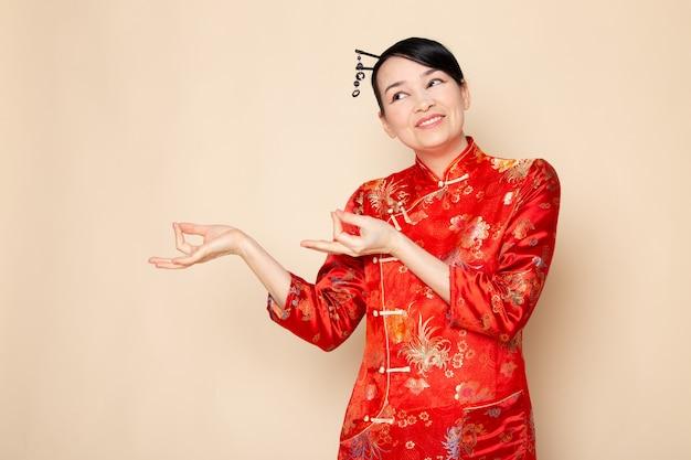 正面を向いて立っている笑顔の日本の伝統的な赤い和服の正面日本の美しい芸者は、日本東部を楽しませてクリーム色の背景に笑みを浮かべて立っているポーズをとって立っています