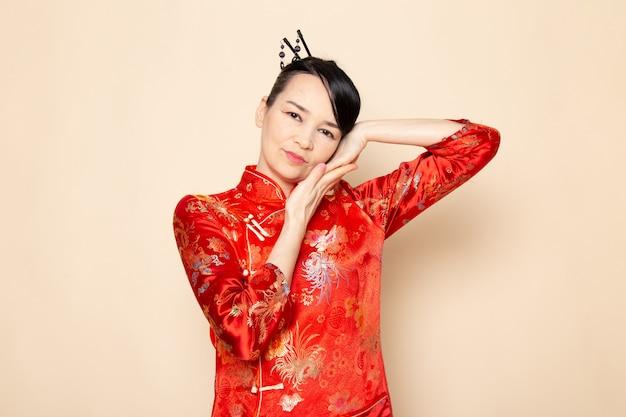 正面が日本東部を楽しませるクリーム色の背景式に彼女の手でポーズをとって髪棒で伝統的な赤い和服で美しい日本の芸者