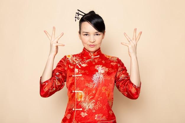 正面東日本を楽しませるクリーム色の背景の上に立って彼女の手でポーズをとって髪棒で伝統的な赤い和服で美しい日本の芸者