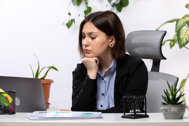 正面は黒いジャケットとテーブルビジネスの仕事のオフィスの前で不安を感じている青いシャツの美しい若い実業家