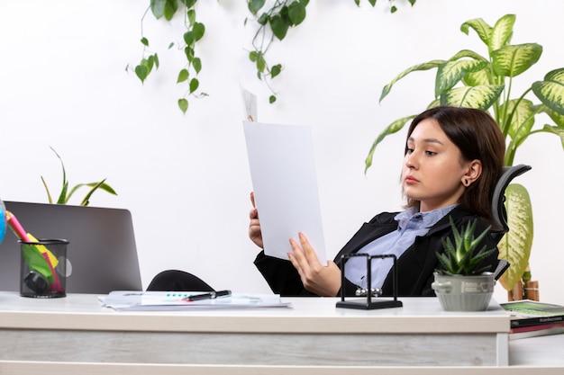 Вид спереди красивая молодая деловая женщина в черной куртке и синей рубашке, работающая с документами перед рабочим столом бизнес-офиса