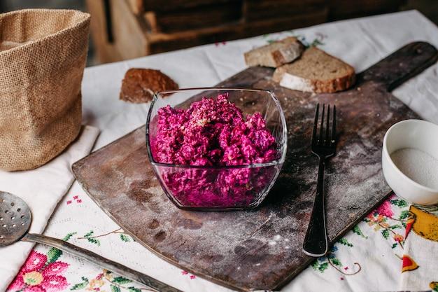 茶色の机の上に透明プレートの塩漬けスパイシーなビタミンおいしい野菜の中でクルミでスライスした正面ビートサラダパープル