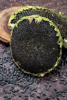 茶色のデスク穀物ヒマワリ種子スナックで新鮮でおいしい正面の黒いヒマワリの種
