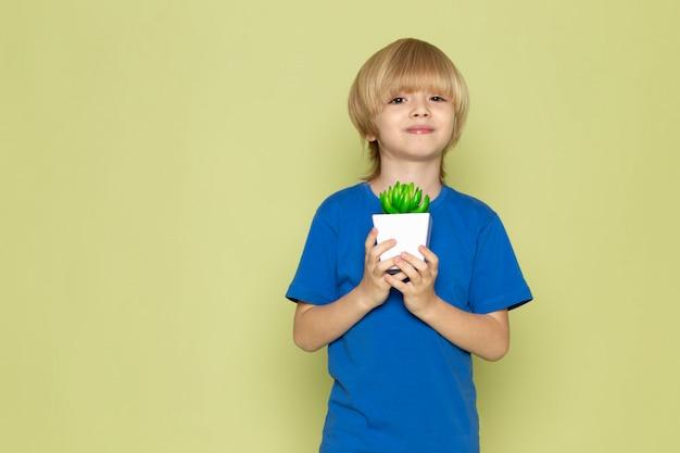 Вид спереди blodne улыбающегося мальчика в синей футболке, держащего маленькое зеленое растение на каменном цветном пространстве