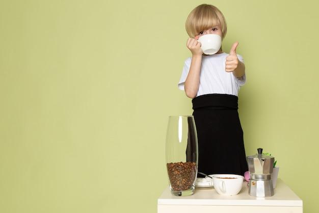 正面の金髪の少年の石の色の机の上の白いtシャツで愛らしい甘いコーヒーを飲む