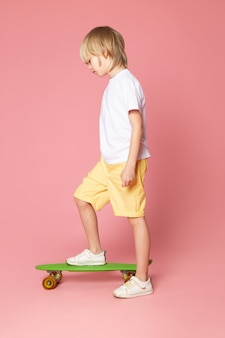 Блондинка спереди в белой футболке и желтых джинсах катается на зеленом скейтборде в розовом пространстве